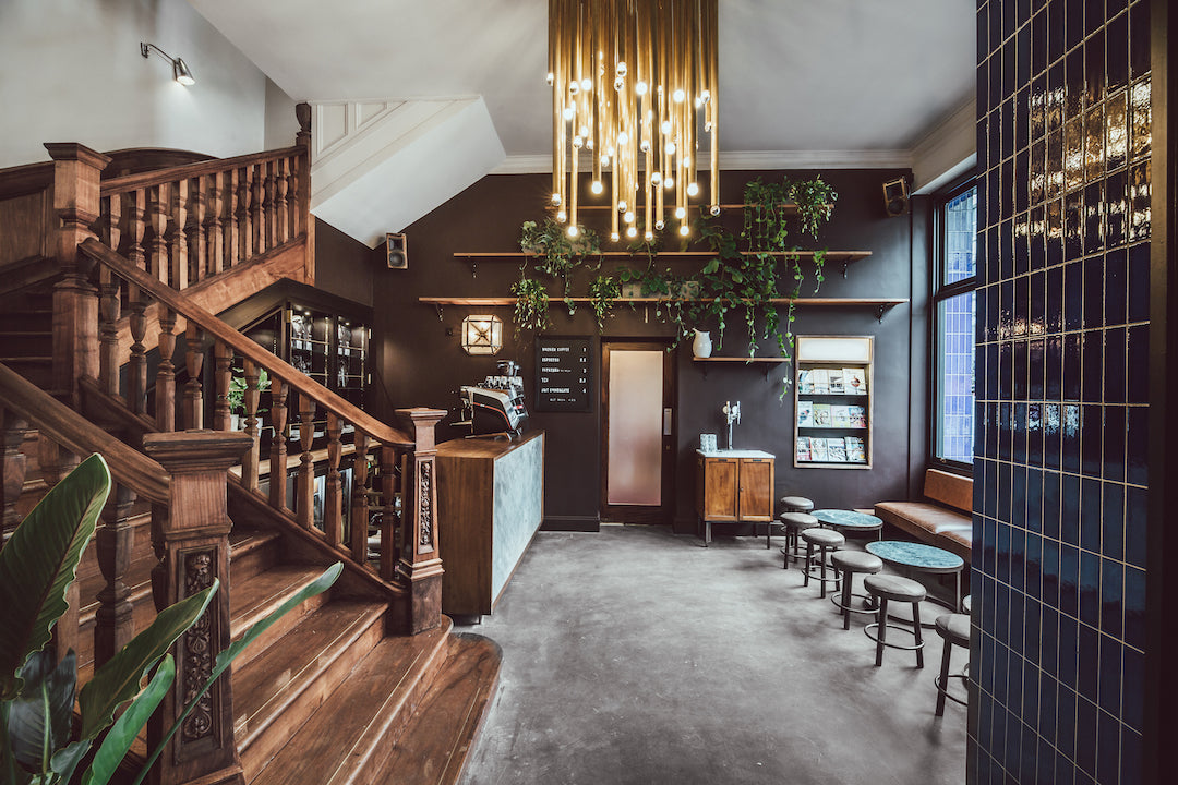 The Pilgrm, London, UK - hotel lobby with a cafe, seating, contemporary chandelier, and Victorian wood staircase