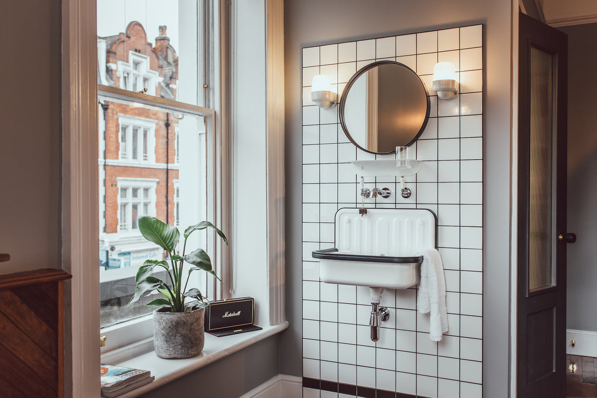 The Pilgrm, London, UK - hotel bathroom with vintage sink, round mirror, and view of London