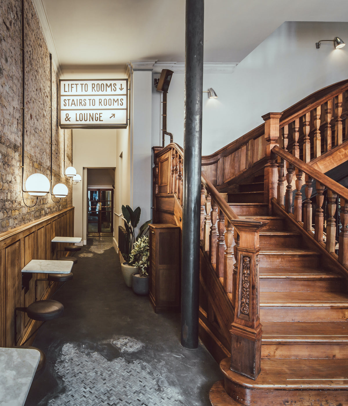 The Pilgrm, London, UK - hotel lobby with modern exposed brick wall and antique Victorian wood staircase