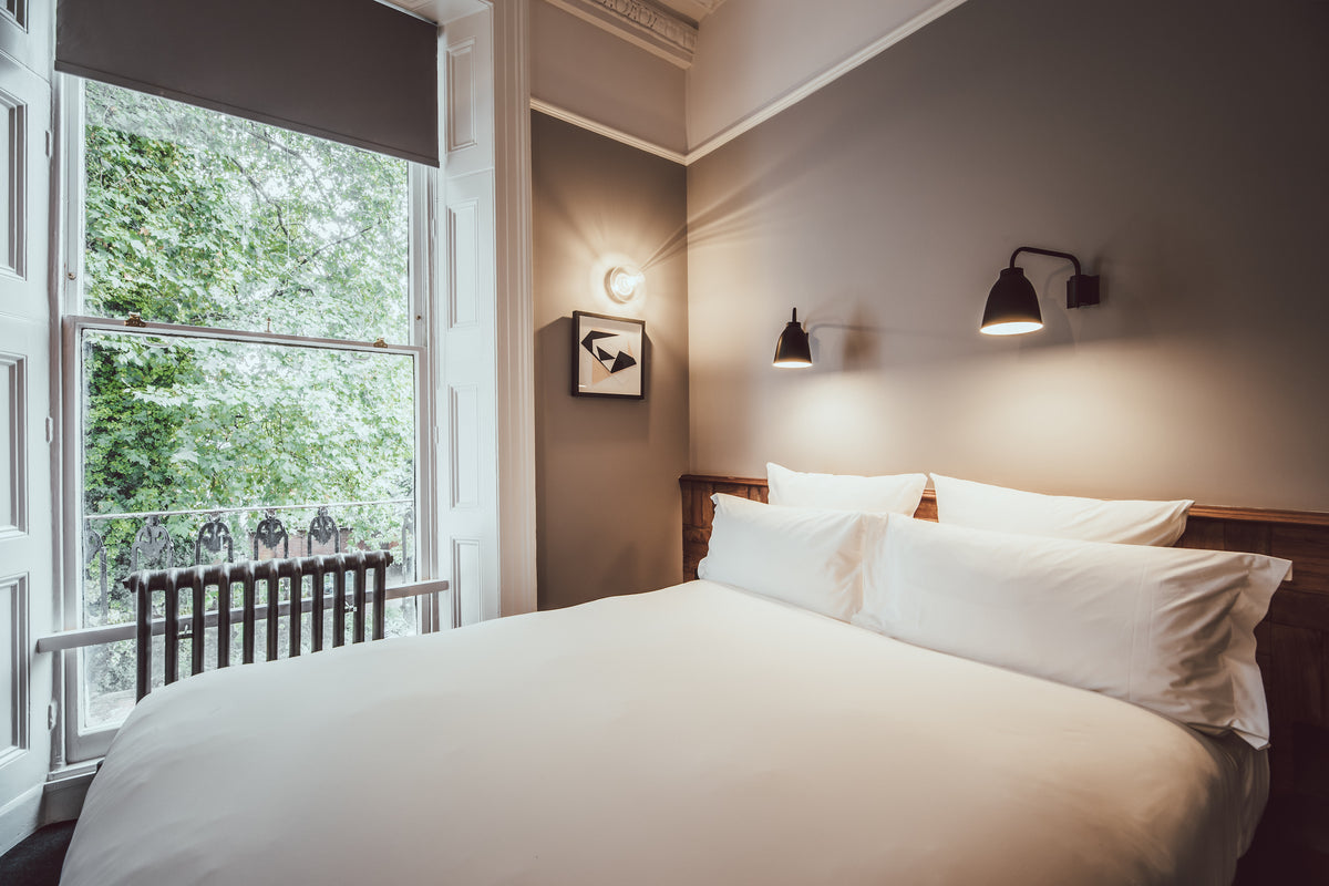 The Pilgrm, London, UK - hotel room with neutral wall and wooden bedframe, overlooking greenery