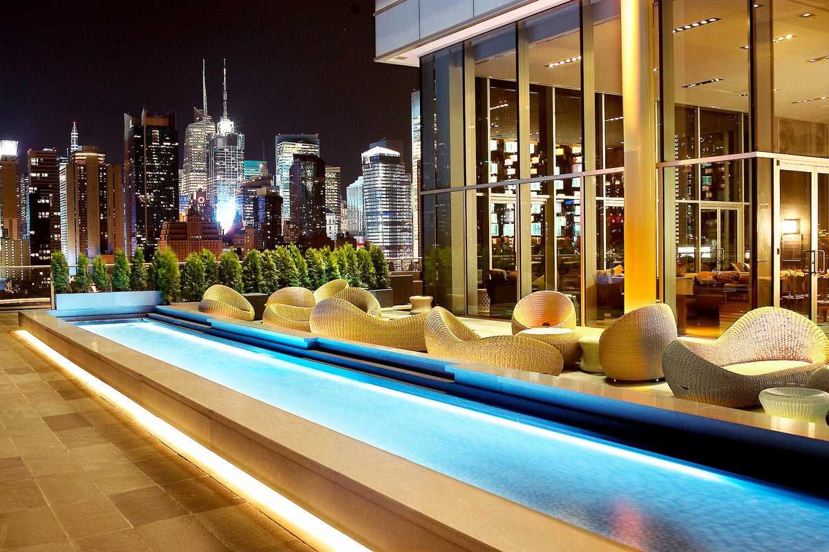 Ink 48, NYC - hotel rooftop at night with pool, contemporary chairs, and city skyline view