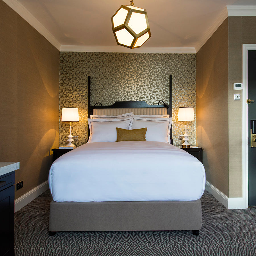 The Academy Hotel, London - modern hotel room with beige walls, golden accent wall, bed, and geometric ceiling light