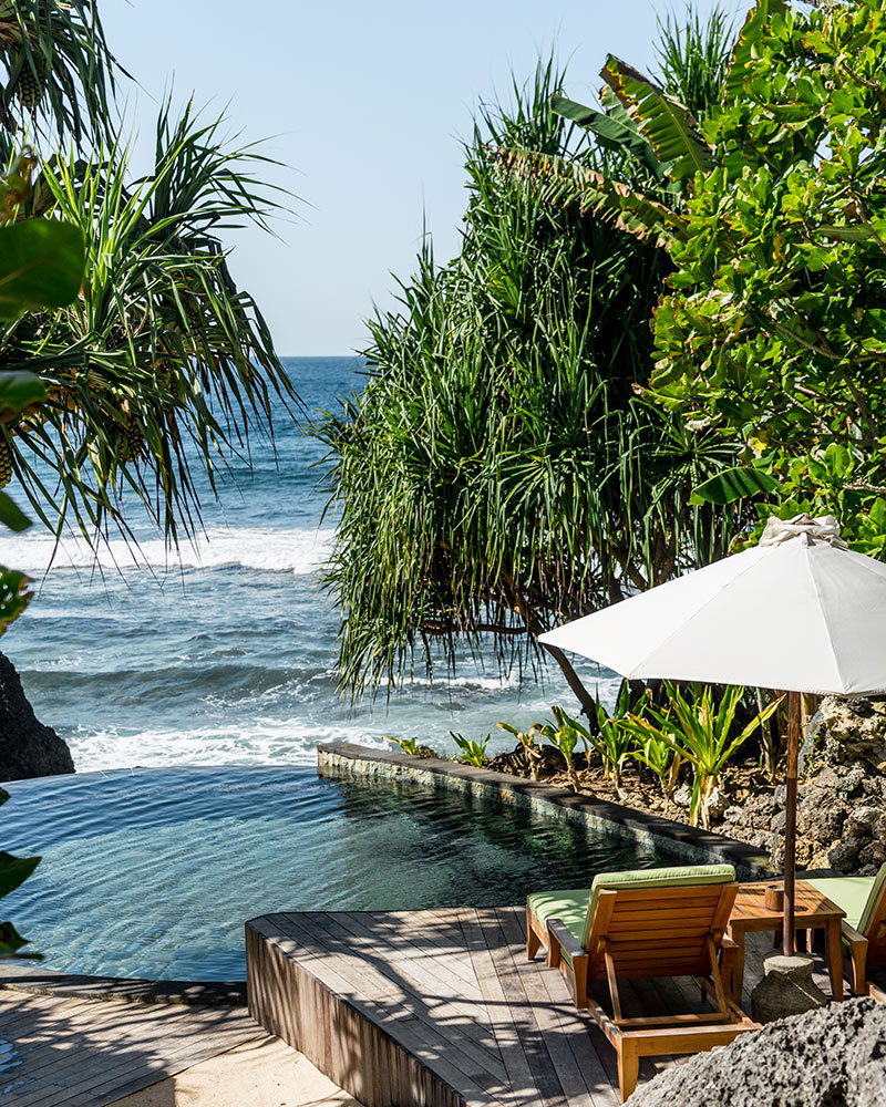 Nihi Sumba, Sumba Island- secluded lounge chairs and sun umbrella overlooking small infinity pool and ocean