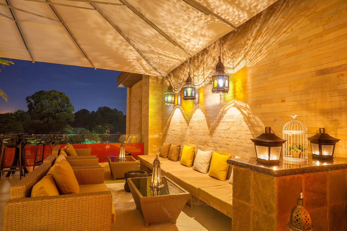 Tribe, Nairobi- lounge ares with Moroccan lamps, couches, and view of forest