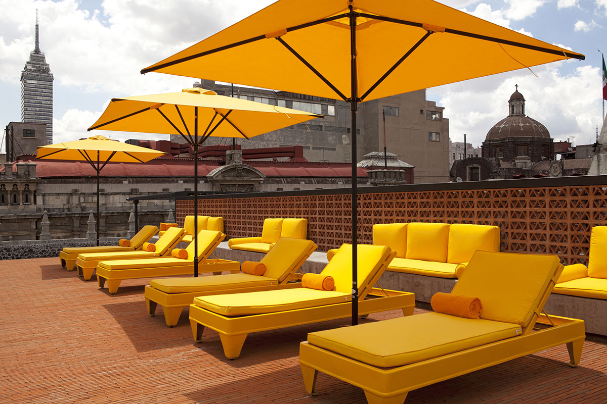 DOWNTOWN, Mexico City - hotel rooftop pool with bright yellow lounge chairs and sun umbrellas with views of Mexico City