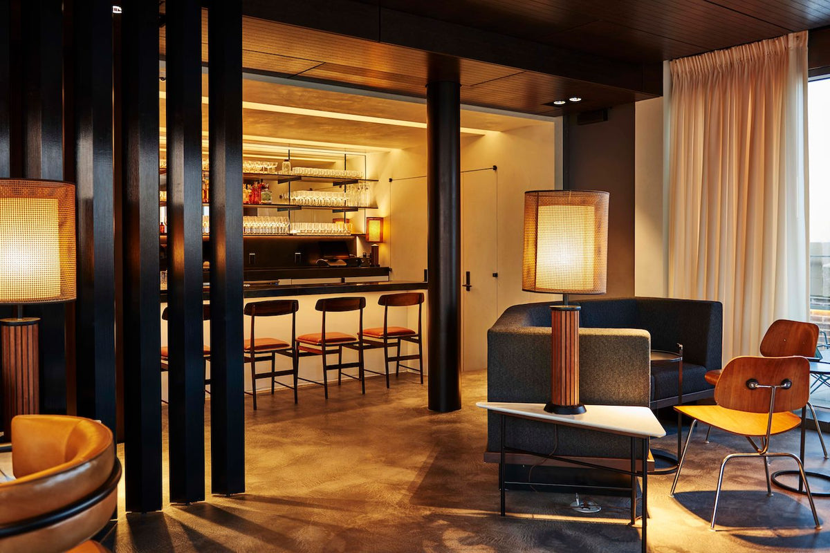 The Robey, Chicago - Up Room bar with wooden chairs, dark armchairs, and stocked bar