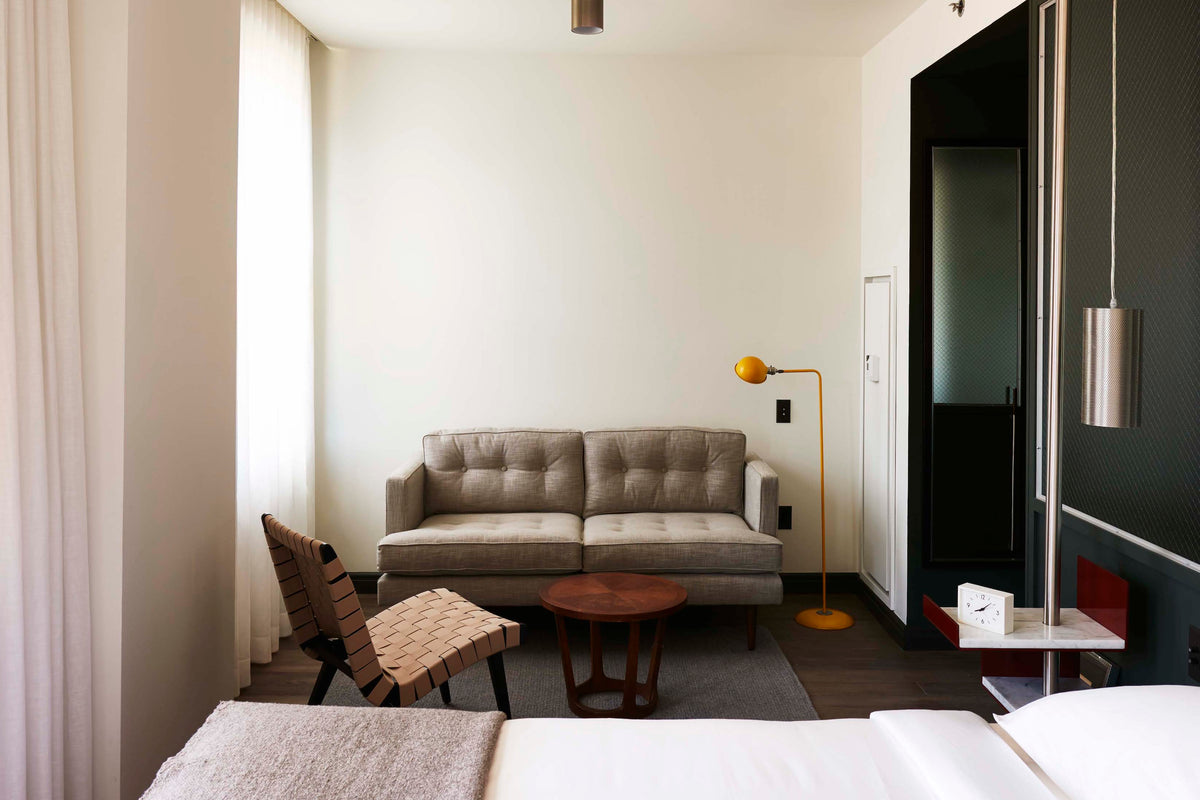 The Robey, Chicago - hotel room with loveseat, coffee table, and minimalist gold lamp