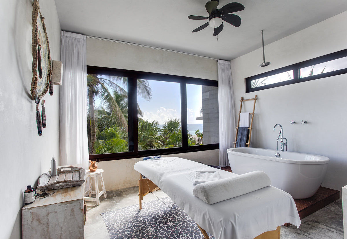 Sanará, Tulum - hotel spa with large tub, massage bed, and window overlooking tropical greenery and turquoise ocean