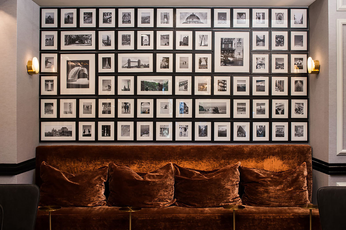 Claridge House, Chicago - brown velvet couch with collage of framed black and white landmark photographs above