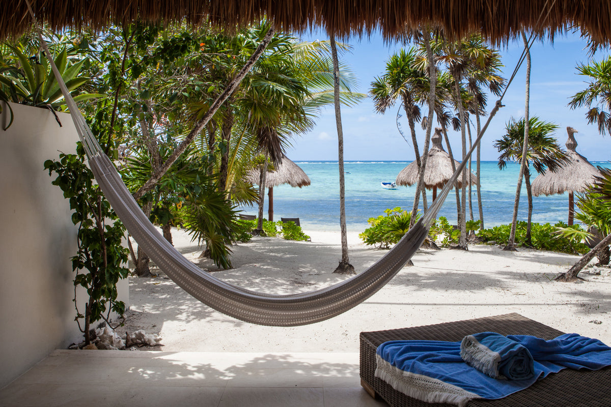 Jashita Hotel, Tulum - thatch roof patio with woven hammock, lounge chair, and view of turquoise ocean
