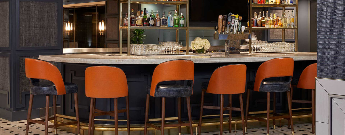 Hutton Hotel, Nashville - West End Kitchen & Bar with marble bar, orange bar stools, and stocked liquor shelves