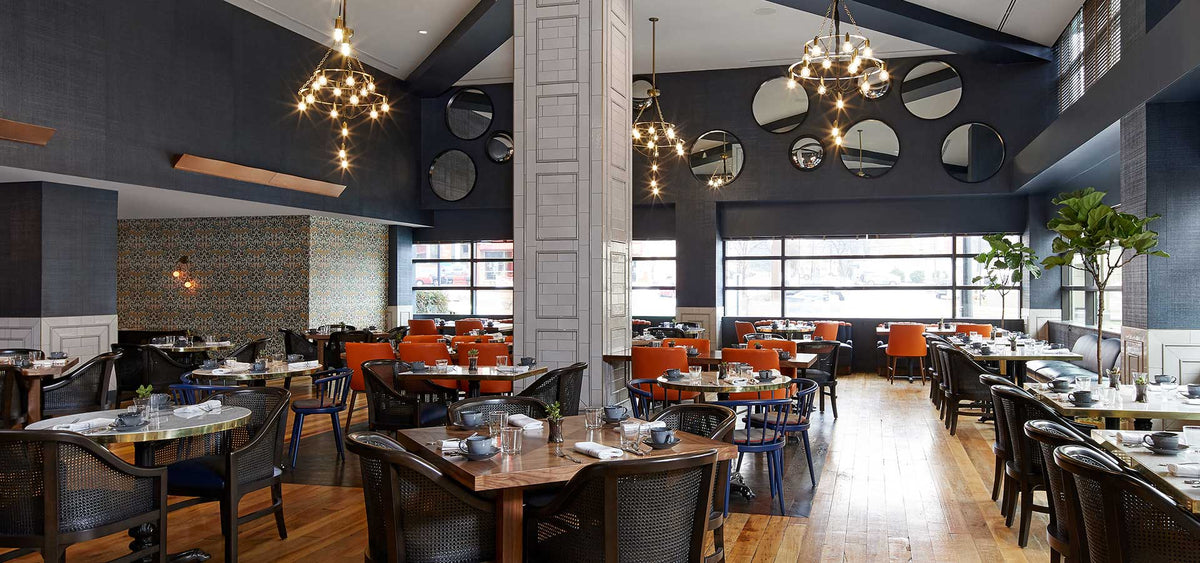 Hutton Hotel, Nashville - Mane & Rye restaurant with set tables, large circle mirror decorations, and chandelier lights