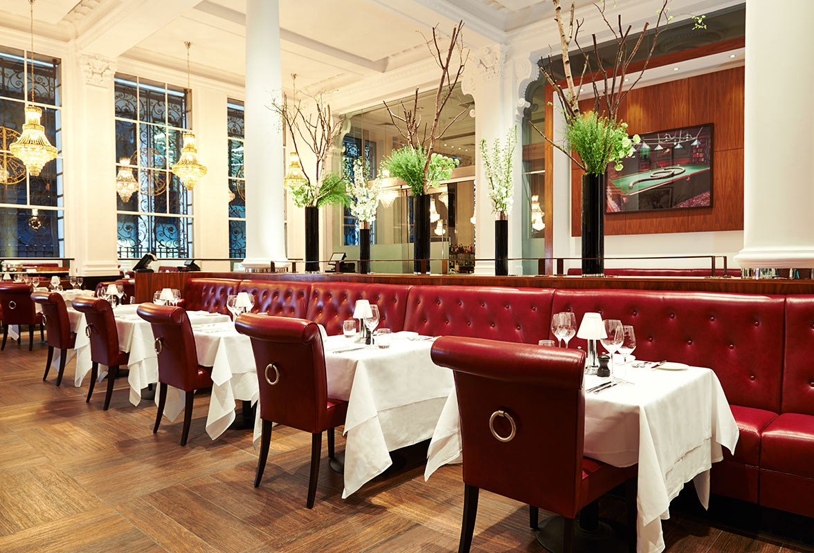 Threadneedles Hotel, London - Marco Pierre White Wheeler's Oyster Bar & Grill Room with red leather couches and chairs and set tables