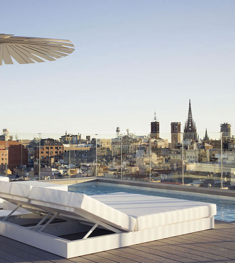 Yurbban Trafalgar, Barcelona - hotel rooftop pool with lounge bed and city view at sunset