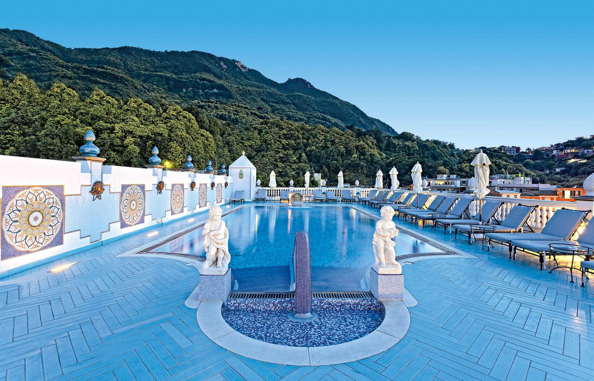 Terme Manzi Hotel & Spa, Ischia - rooftop pool with small marble statues, mosaic tiling, lounge chairs, and sun umbrellas at sunset
