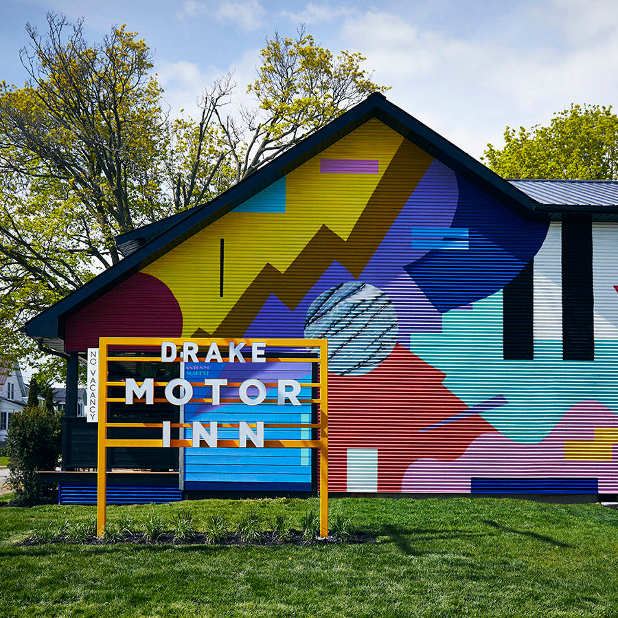 Drake Motor Inn, Prince Edward County - exterior of a brightly painted hotel building with a large letter name sign