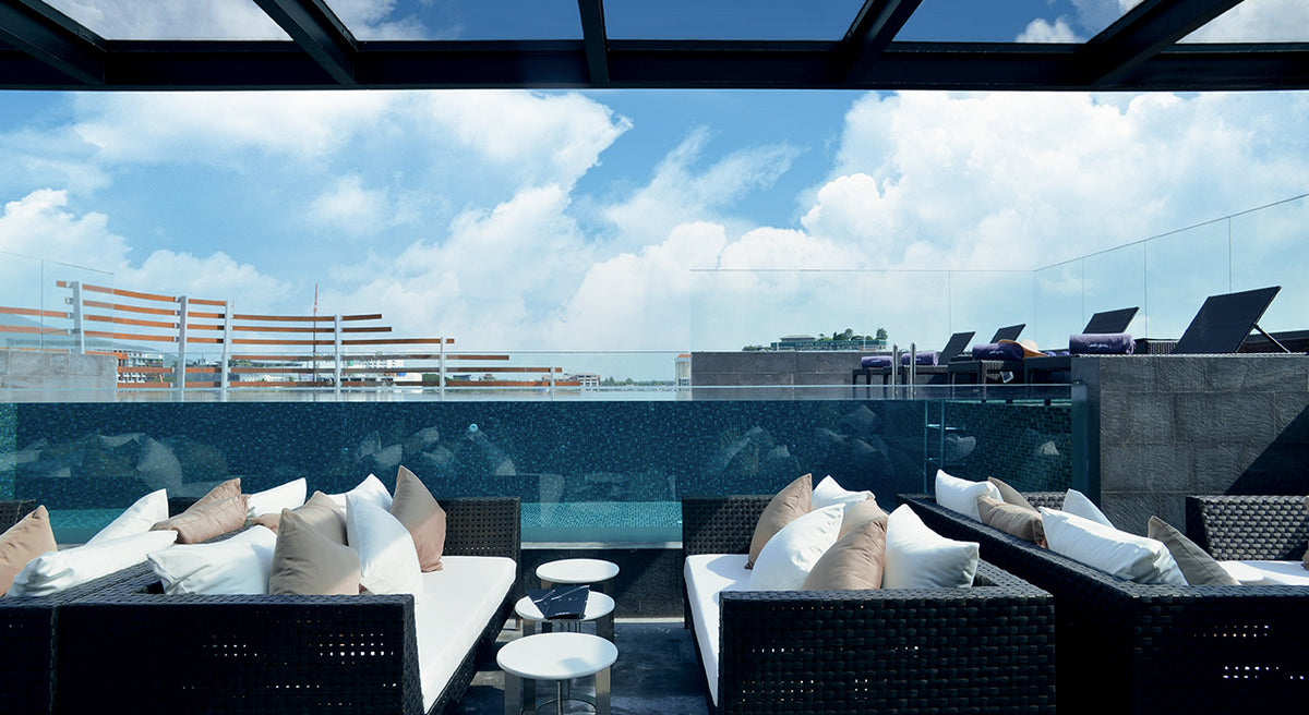 Akyra Manor, Chiang Mai - rooftoop lounge with couches, tables, a glass pool, deck chairs, and a city skyline view