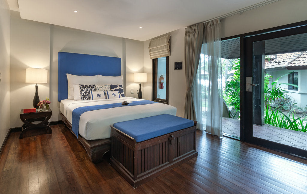 Akyra Beach Resort, Phuket - hotel room with a queen size bed and a door leading to a patio
