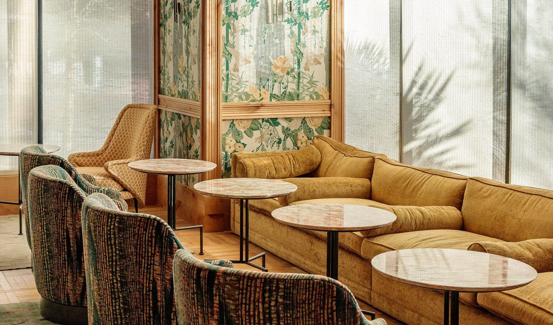 Austin Proper Hotel, Austin - vintage lounge with yellow couch, marble round tables, and patterned armchairs