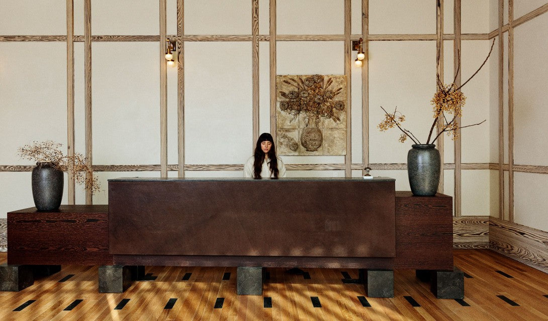 Austin Proper Hotel, Austin - dark wooden reception desk with an employee behind and two large potted plants on both sides