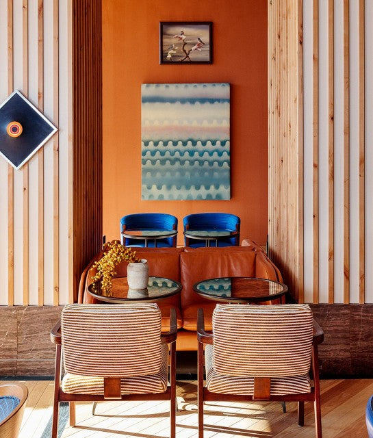 Austin Proper Hotel, Austin - colorful lounge with orange walls, wooden beams, a leather couch, and striped armchairs
