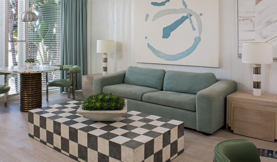 Avalon Hotel Beverly Hills, Los Angeles - hotel room with a green couch, checkerboard coffee table, and retro decor