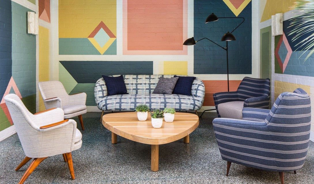 Avalon Hotel Beverly Hills, Los Angeles - hotel lounge with retro geometric painted wall, couch, armchairs, lamp, and coffee table with potted succulents