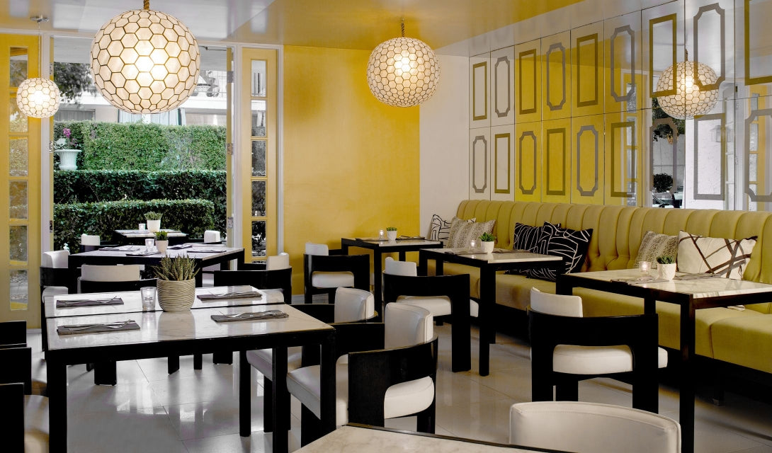 Avalon Hotel & Bungalows, Palm Springs - hotel restaurant interior with black and white tables and chairs and yellow walls