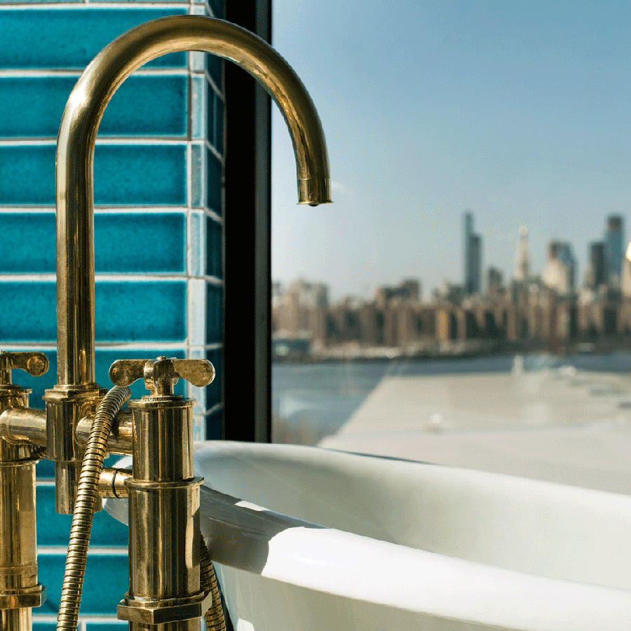The Williamsburg Hotel, NYC -  close up of hotel bath with golden faucet and window overlooking East River and NYC skyline