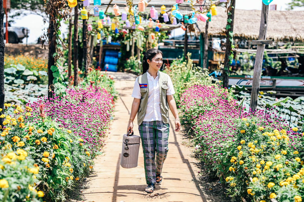 Bensley Collection Shinta Mani, Siem Reap - woman walking down a flower-lined path with wooden arches and colorful lanterns
