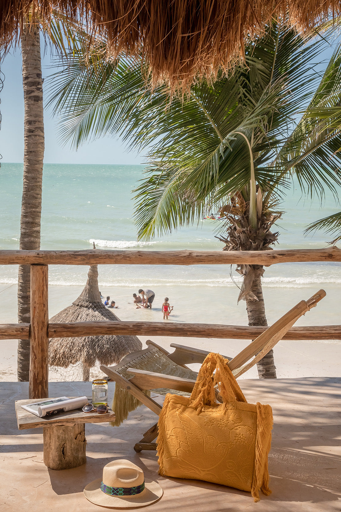 Casa Cat Ba, Isla Holbox - patio with a thatch roof, a macramé rocking chair, yellow beach bag, and beach view