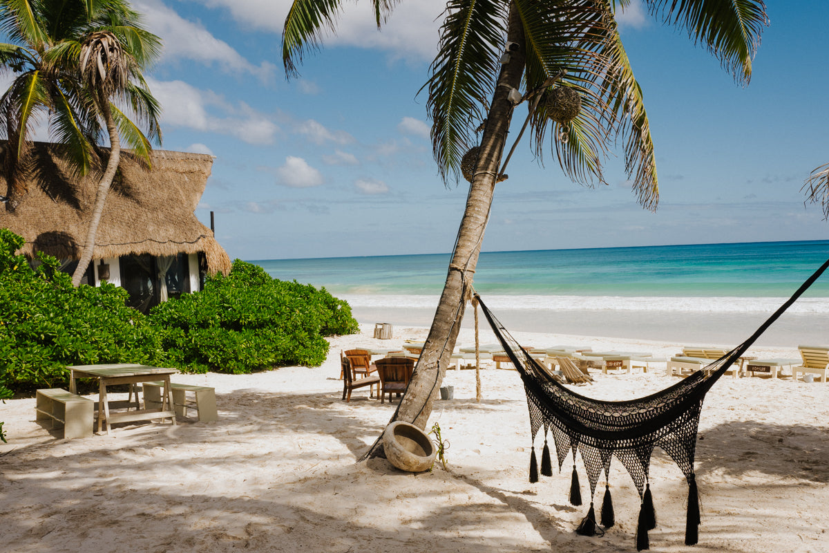 Casa Violeta, Tulum - beach scene with a palm tree hammock, picnic bench, lounge chairs, and blue ocean