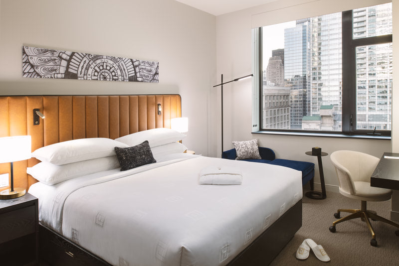 Hotel Julian, Chicago - hotel room with a bed, leather headboard, floor lamp, bedside lamp, desk, chair, and window overlooking city view