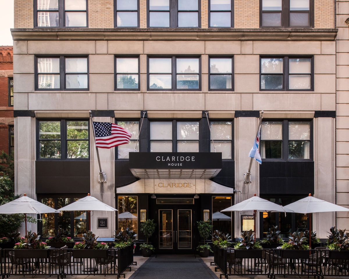 Claridge House, Chicago - hotel exterior of a light stone building with a patio in front and white sun umbrellas