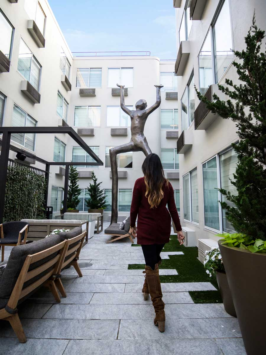 Hotel Zoe Fisherman's Wharf, San Francisco - woman walking in a hotel courtyard with a large statue of a person
