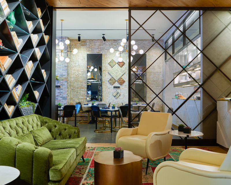 Hotel Julian, Chicago - hotel lounge with diamond pattern bookshelf, green velvet couch, and tan leather armchairs