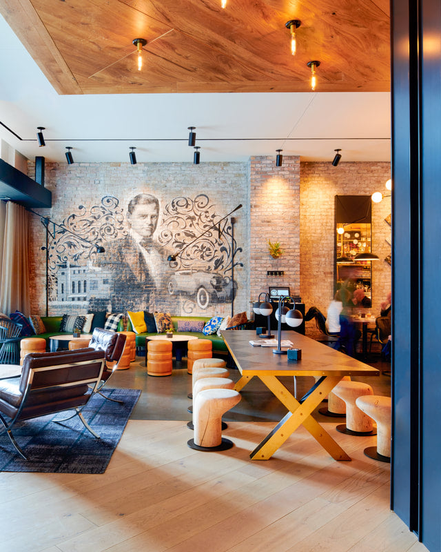 Hotel Julian, Chicago - hotel lobby with eclectic wood furniture, wood paneled ceiling, and a large brick wall mosaic
