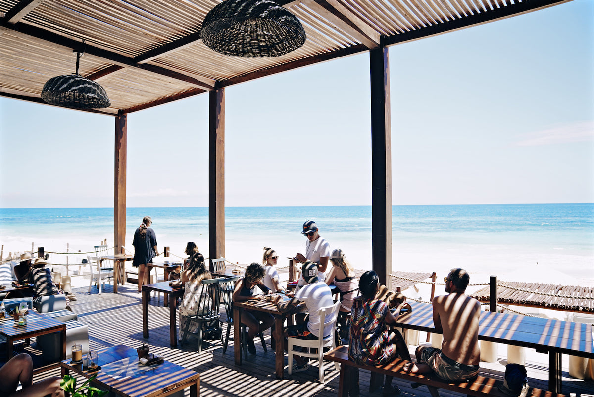 Sanará, Tulum - The Real Coconut restaurant patio with people dining and a view of the turquoise ocean