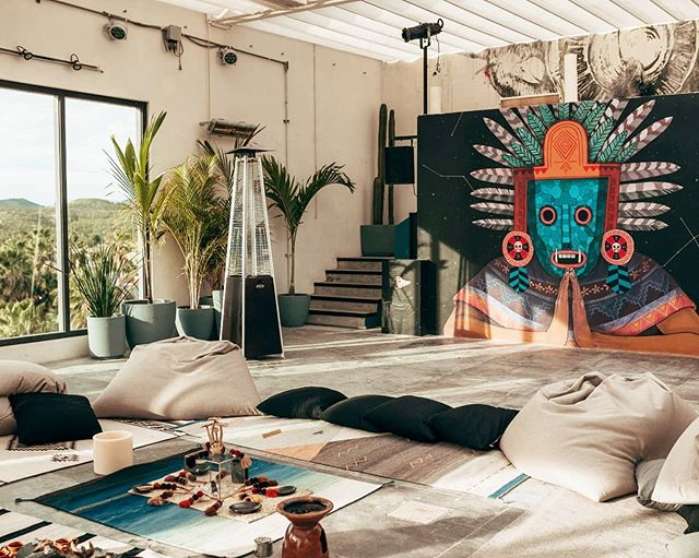 Hotel El Ganzo, Los Cabos - hotel lounge with woven rugs, bean bag cushion seats, large jungle view windows, and a Mexican wall mural