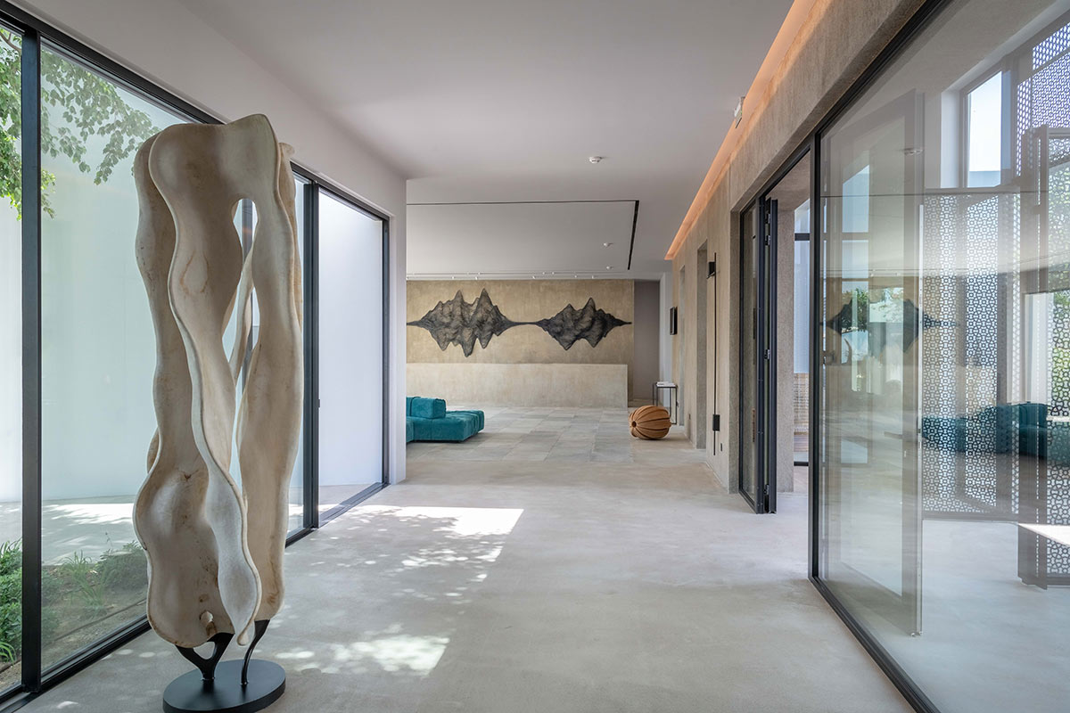 Minos Beach Art Hotel, Crete - hotel hallway with abstract sculpture and floor to ceiling sliding windows on both sides
