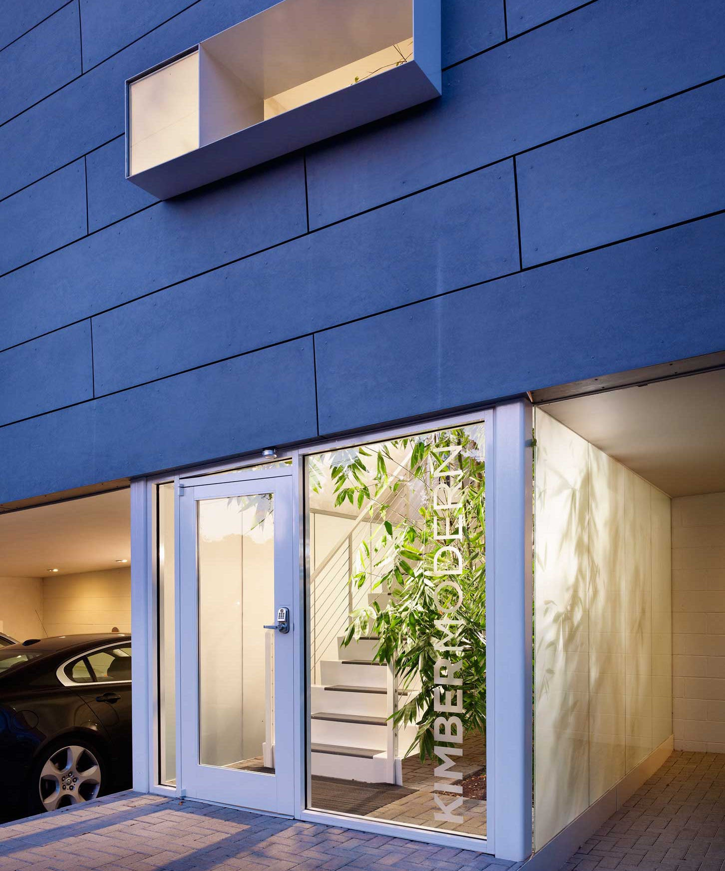 Kimber Modern, Austin - hotel exterior with contemporary glass door and blue siding
