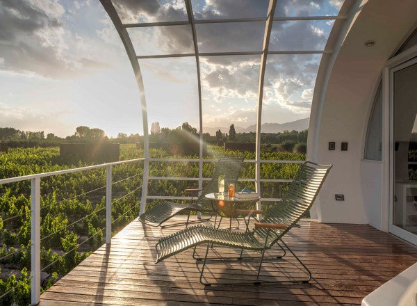 Entre Cielos, Mendoza - patio with lounge chairs above a vineyard at sunset