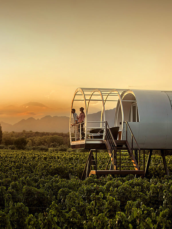 Entre Cielos, Mendoza - white tubular structure with two people standing on its balcony above a vineyard at sunset