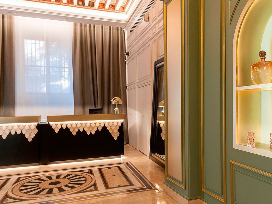 Hotel Eugenia de Montijo, Toledo - hotel reception desk with green moulded wall and ornate tiling
