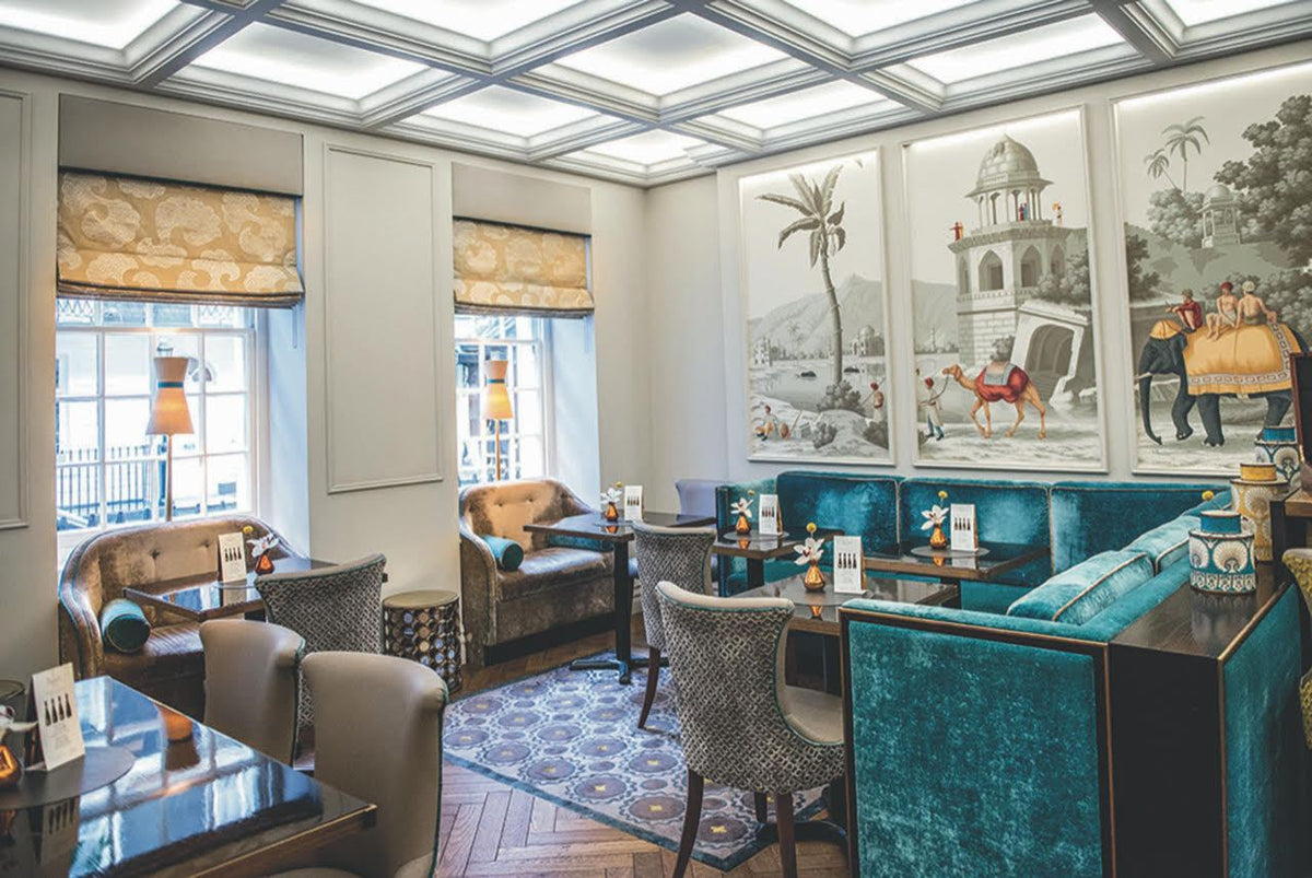 Flemings Mayfair, London - hotel restaurant with teal couches, grey chairs, dark wood tables, and large wall art scene