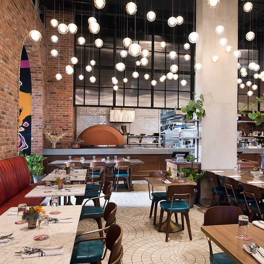 The Williamsburg Hotel, NYC - Seven Seeds restaurant with hanging light bulbs, colorful chairs, and set tables