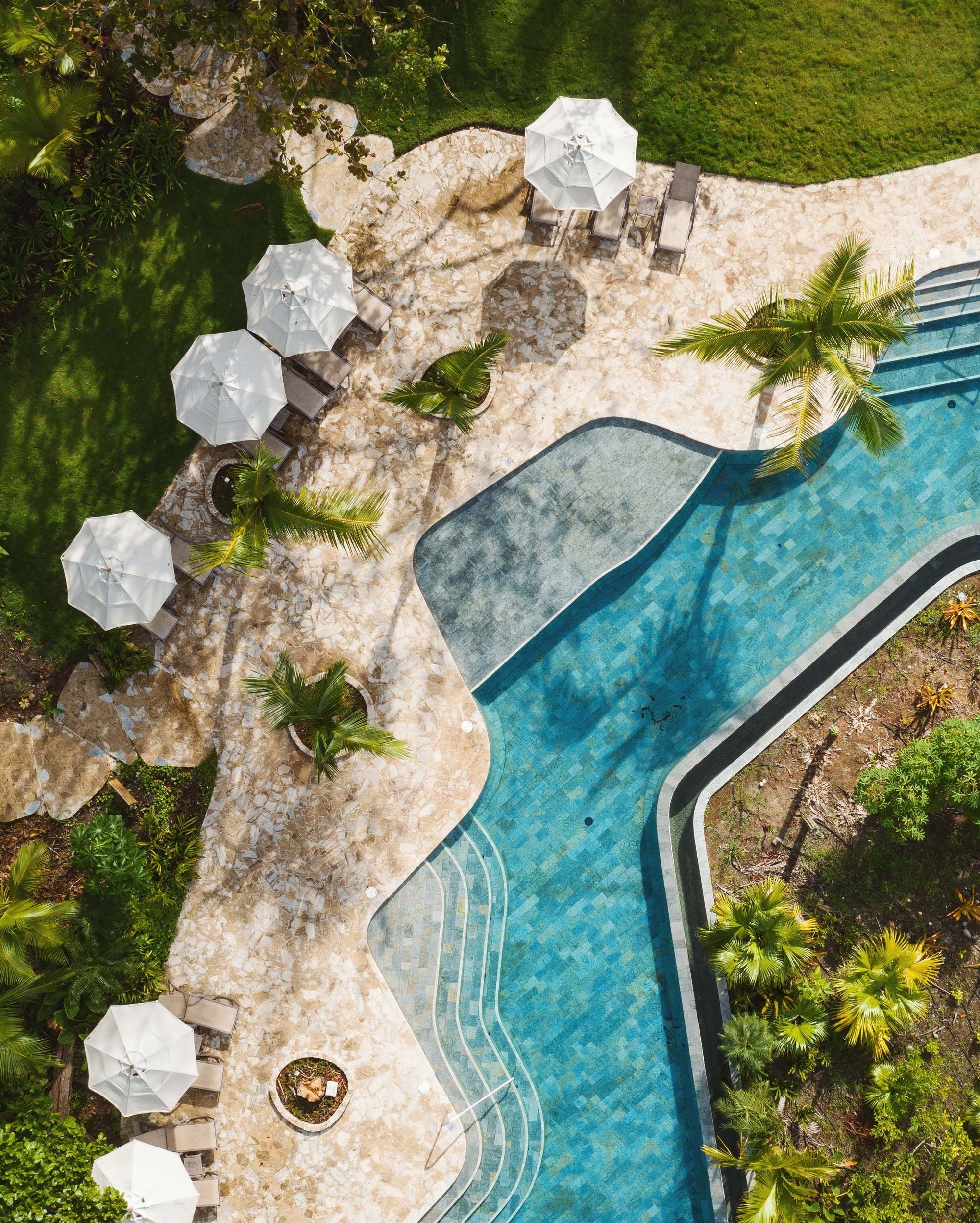 Nantipa, Santa Teresa, Costa Rica - birds eye view of a geometric pool with sun umbrellas, palm trees, and greenery