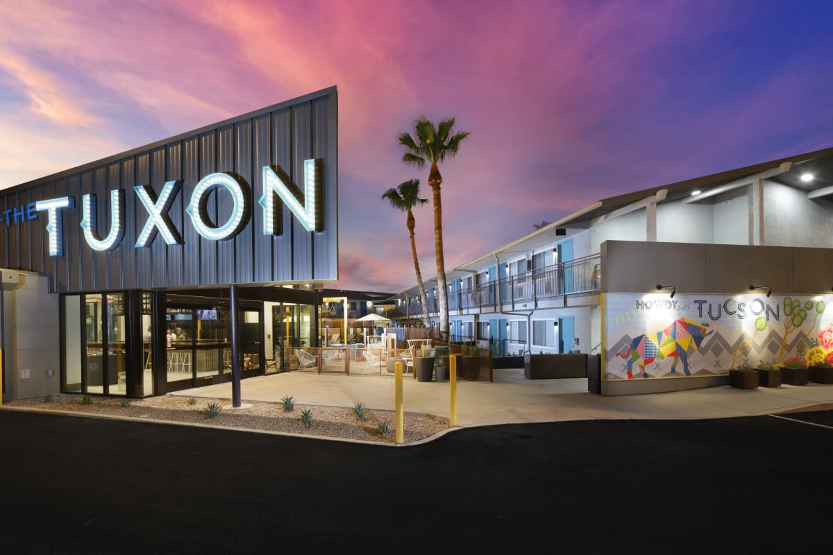 "The Tuxon Hotel, Tucson - hotel exterior at sunset with huge black sign and white neon lights ""Tuxon"""