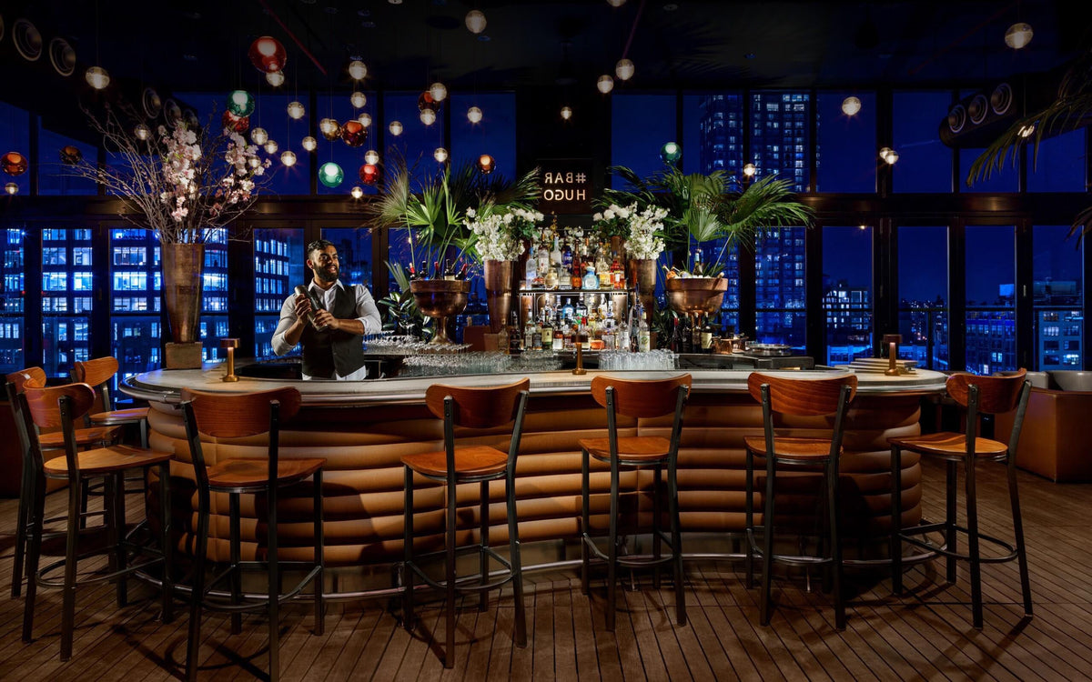 Hotel Hugo, NYC - Bar Hugo with a bartender making a drink, wooden barstools, and hanging colorful orb lights