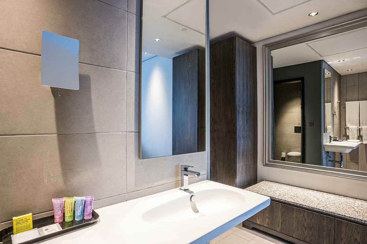 Trademark, Nairobi - sleek hotel bathroom with sink, mirrors, stone walls, and toiletry products